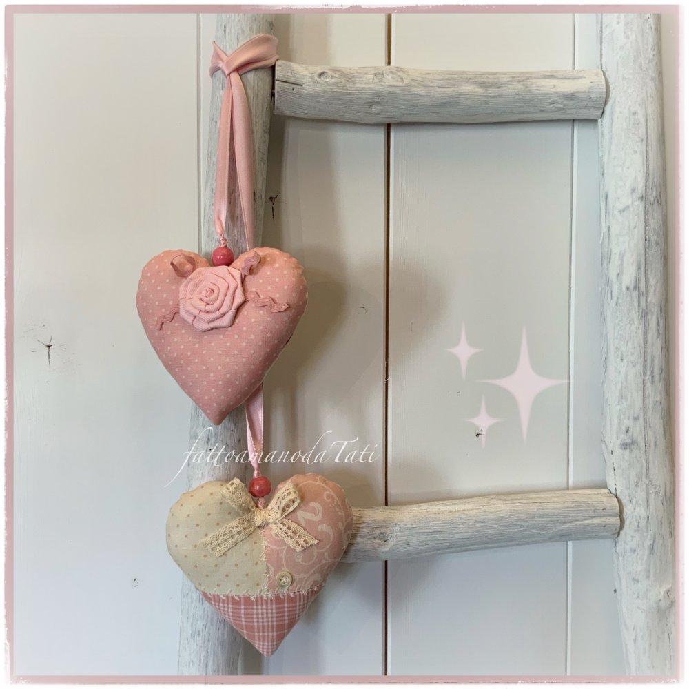 Decorazione per bimbe formata da due cuori in cotonine fantasia sui toni del rosa uniti da nastrino di raso rosa
