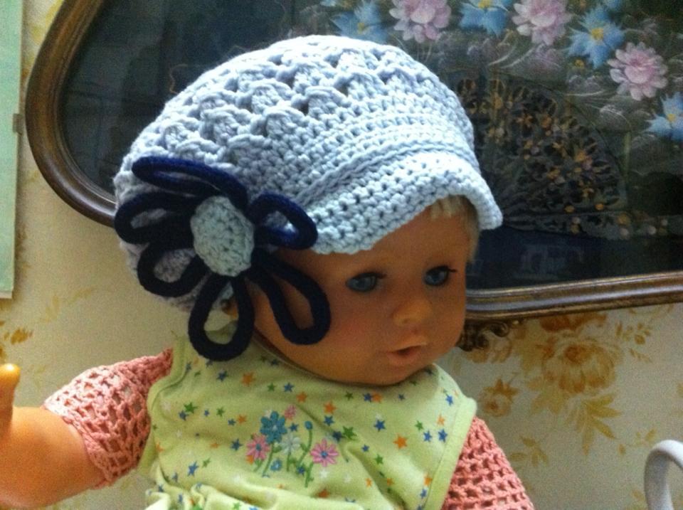 Cappello con visiera bicolore  all'uncinetto con fiore