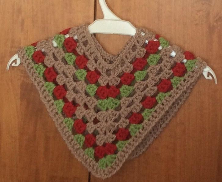Poncho crochet per bambina di 12-16 mesi color camoscio, rosso bordeaux e verde.