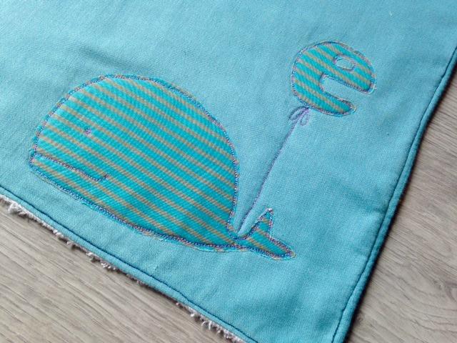 Asciugamano personalizzato per il fasciatoio con il monogramma del bambino appeso ad una dolce e morbida balena