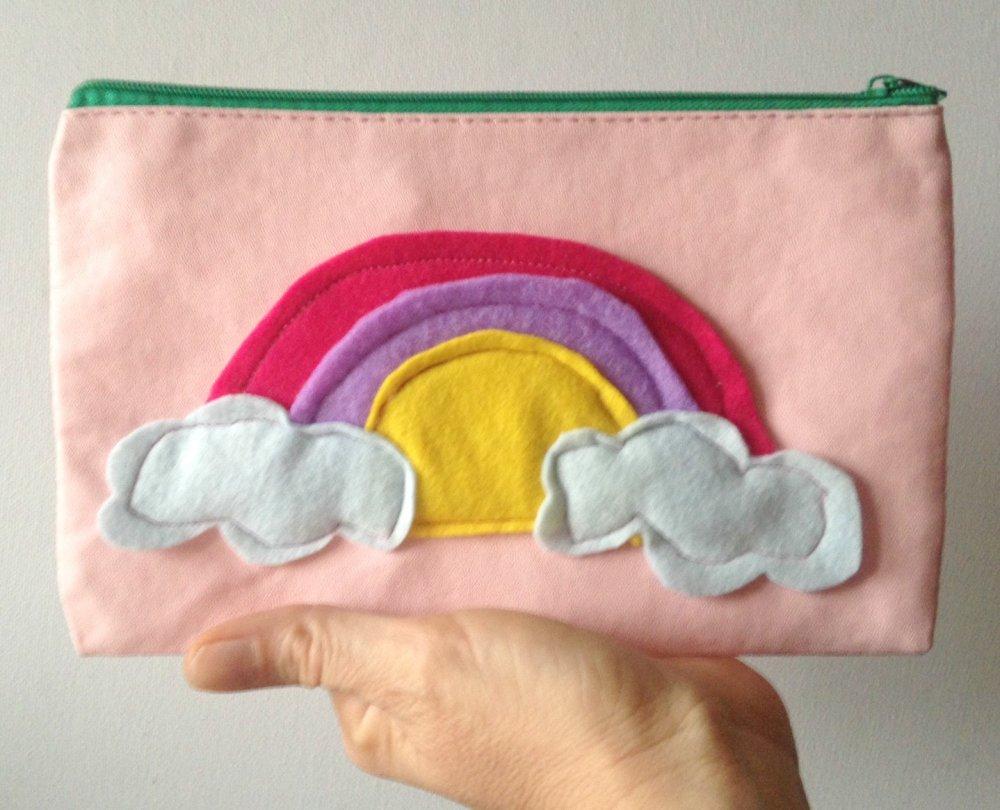 Pochette in eco pelle rosa con un arcobaleno colorato e zip verde