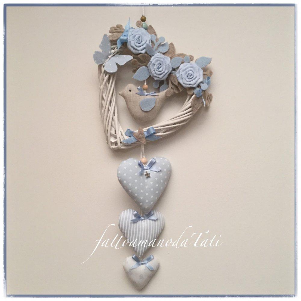 Cuore/fiocco nascita in vimini con roselline,farfalla,uccellino e tre cuori sui toni dell'azzurro/beige