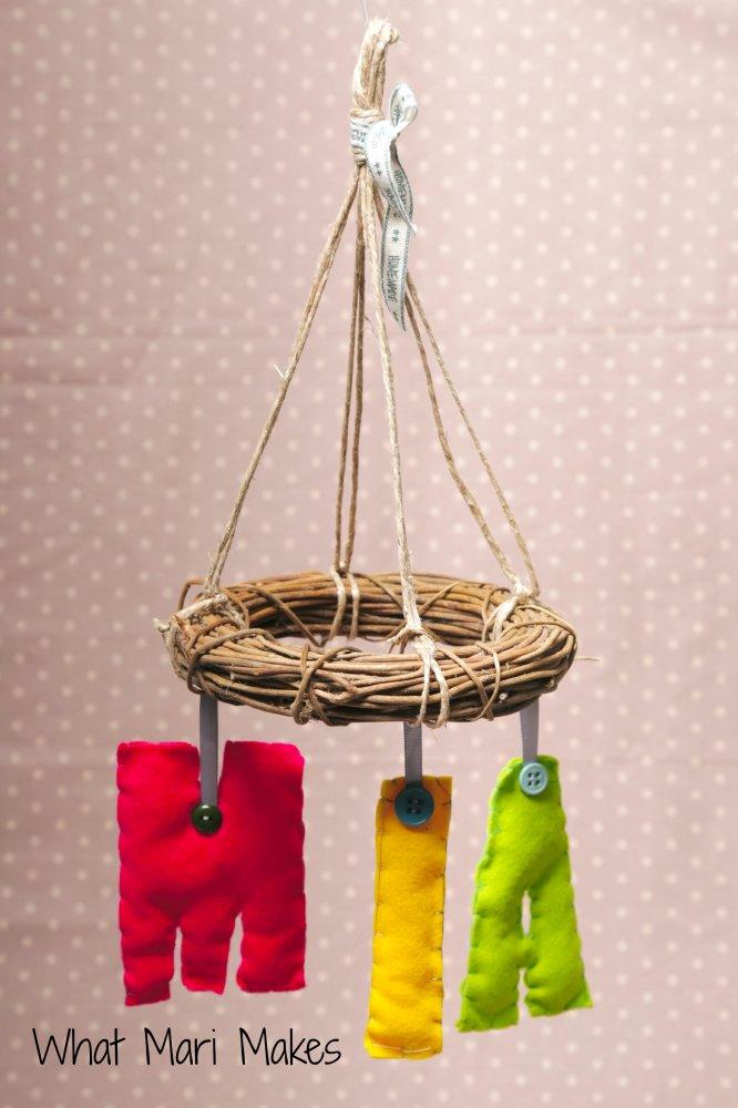 Giostrina per  culla del bebe' o per la cameretta del bimbo in vimini e morbide letterine di feltro cucite a mano