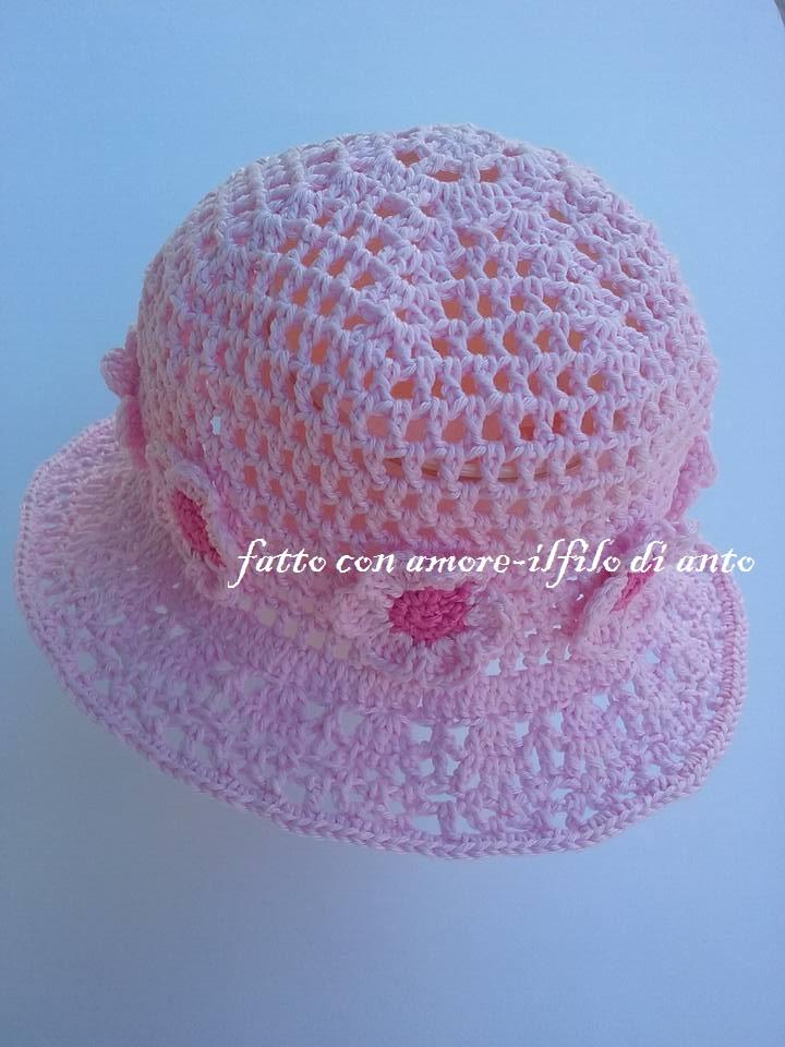 Cappello  rosa  traforato con tesa e  fiori bianchi