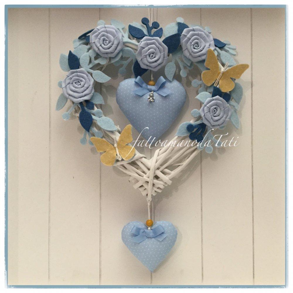 Cuore/fiocco nascita in vimini con roselline,rametti ,due cuori azzurri e due farfalle gialle